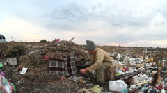 Man unemployed homeless dirty looking food dump waste in landfill  social video Stock Footage