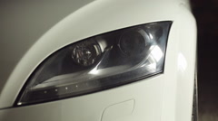 Close-up of headlights of white car in garage - stock footage