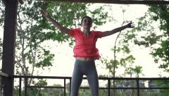 Woman exercising, doing jumping jacks on house porch Stock Footage