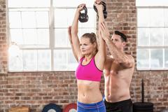 Attentive muscular trainer show how to lift kettlebells Stock Photos