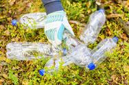 Stock Photo of Man picking up used plastic bottles in forest
