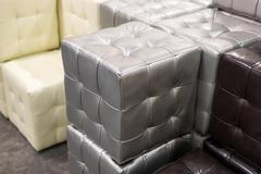 Many leather footstools of different colors in  stack - stock photo