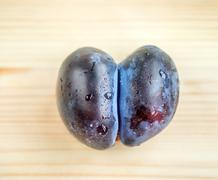 Ripe washed and fresh plum original forked shape on a wooden table close-up.  - stock photo