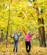 Happy beautiful little children throw up autumnal leafage in park - stock photo