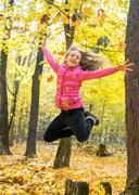 Happy beautiful young girl throw up autumnal leafage and high jump in the aut - stock photo