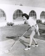 Side view of  woman playing shuffleboard - stock photo