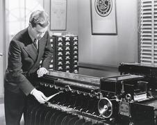 Man operating fingerprint sorting machine - stock photo