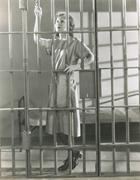 Young woman standing in prison cell - stock photo