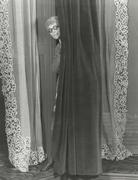Woman eavesdropping from behind curtain - stock photo