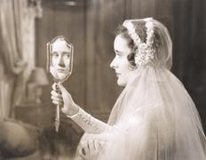 Bride gazing into hand mirror - stock photo