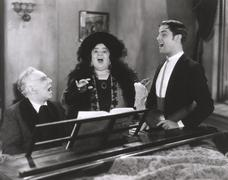 People singing at piano Stock Photos