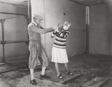 Trainer teaching woman to play golf Kuvituskuvat