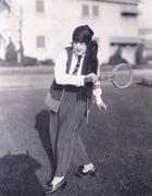 Woman playing badminton outdoors - stock photo
