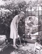 Woman playing miniature golf - stock photo