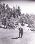 Man smoking pipe while playing golf - stock photo
