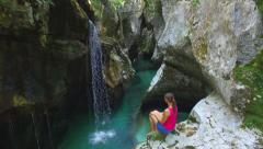 Stock Video Footage of AERIAL: Young woman sitting on the edge of river canyon