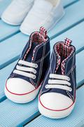Pairs of Dark Blue, White Baby Sneakers and Blue Baby Shoes - stock photo