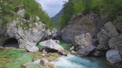 AERIAL: Beautiful blue mountain river running through the rocky valley - stock footage