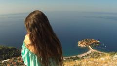 Beautiful brunette Girl with Healthy Long Hair relaxing on rock above island Stock Footage