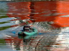 The Colorful reflection on water and fisherman in boat. - stock photo