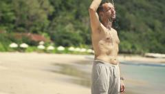 Handsome male jogger drinking water and cooling himself on the beach HD - stock footage