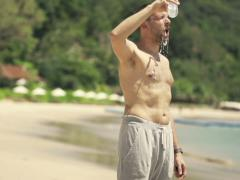 Handsome male jogger drinking water and cooling himself on the beach NTSC - stock footage