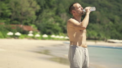 Young male jogger drinking water on the beach, shot at 240fps HD - stock footage