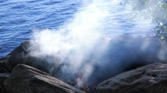 Dense smoke spreading as dried leaves are thrown into the fire Stock Footage