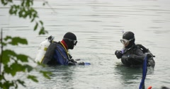 Two Men Divers in Swimsuits Are Standing in The Water Checking the Equipment Stock Footage