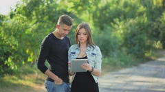 Couple in love looking at the photos on the tablet Stock Footage