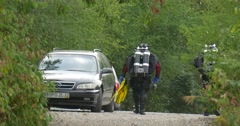 Two Men Divers in Swimsuits Are Walking Away by the Footpath Green Trees along Stock Footage