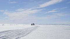 Snowmobile towing a qamutik on sea ice toward the camera. Stock Footage