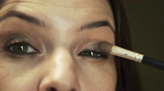 Closeup of woman applying makeup eyeshadow in front of the mirror HD Stock Footage