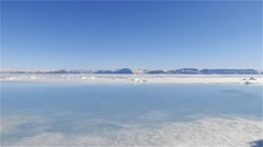 Landscape and with a melt pond in the foreground and mountains in the Stock Footage