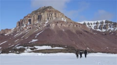 Expeditioners walking toward the base of a mountain. Stock Footage