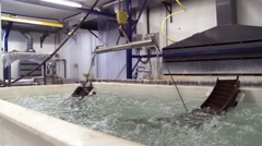 An aircraft component is lifted from a chemical bath. - stock footage