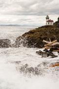 Waves Crash onto Sharp Rocks Jetty San Juan Island Lighthouse - stock photo