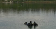 Three Divers Distantly Are Standing in The Water Checking their Equipment Going Stock Footage