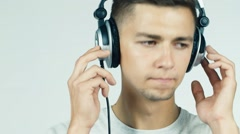 Man listening to music with headphones on a white background Stock Footage