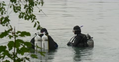 Two Men Divers Are Standing in The Water One Man Has Surfaced Three Divers are Stock Footage