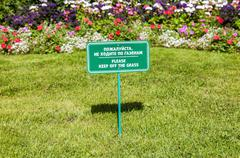 """Notice board on the lawn with text """"Please keep of the grass"""" - stock photo"""
