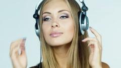 Girl in headphones listens, asks, laughing - stock footage