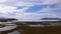 Arctic Bay, Nunavut landscape with sea-ice and mountain ranges in the distance. - stock footage