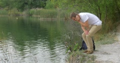 Man Tourist Man in White T-Shirt Man With Backpack is Sitting at the River Bank Stock Footage