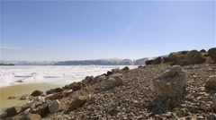 Arctic Bay landscape with sea-ice melting along the shoreline. (Pan Left) - stock footage
