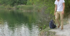 Man Tourist Man in White T-Shirt Man With Backpack at the River Bank Rippling Stock Footage