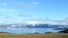 Clouds moving quickly over a mountains and sea ice in Arctic Bay Nunavut. - stock footage