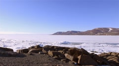 Shoreline in Arctic Bay with a lead running through the sea-ice. (Pan Left) - stock footage