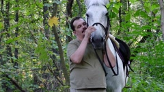 Handsome smiling man petting his beautiful horse Stock Footage
