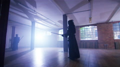 4K Japanese kendo fighters with bamboo swords competing in dark building Stock Footage